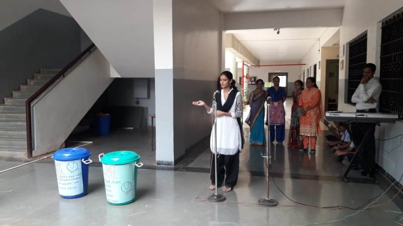 arrengement of blue and green dustbins in school