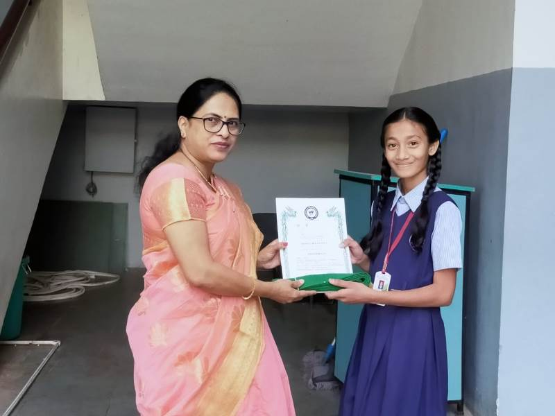 Awarded by Principal Mam with certificate & green belt in Karate Exam