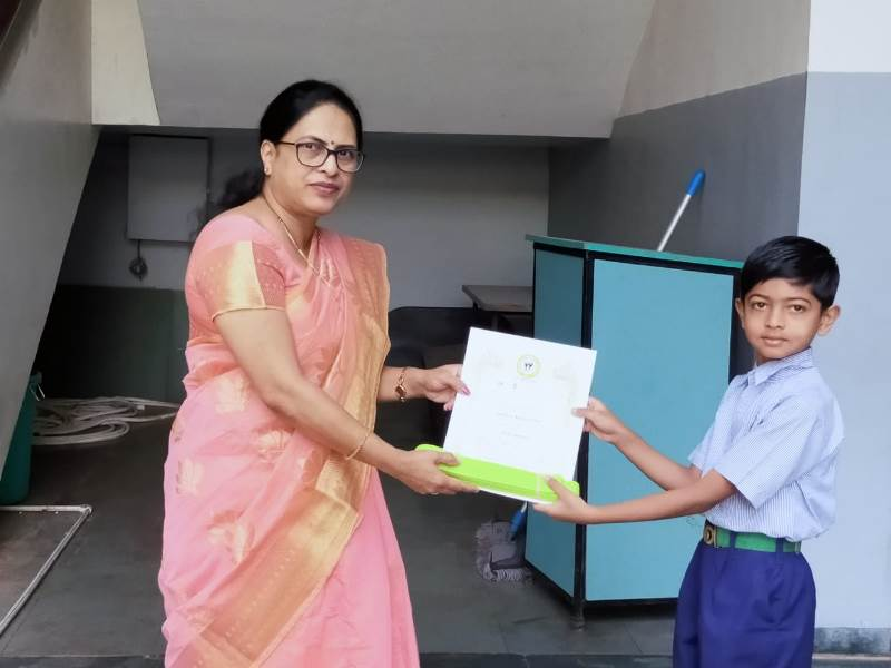 Awarded by Principal Mam with certificate & yellow belt in Karate Exam