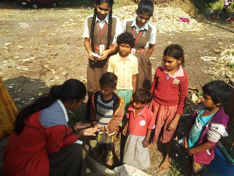Girls showing correct method of washing hands to Sugarcane worker\'s Children