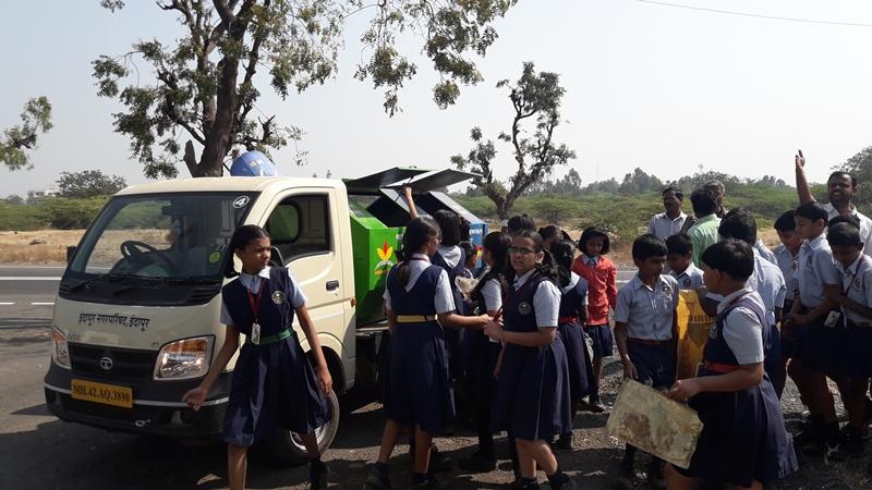 Students dumping plastic in garbage van