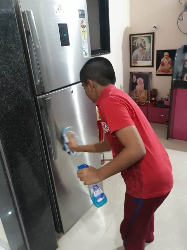 Cleaning refrigerator with wet cloth. Omraje Sarangkar from 4th B
