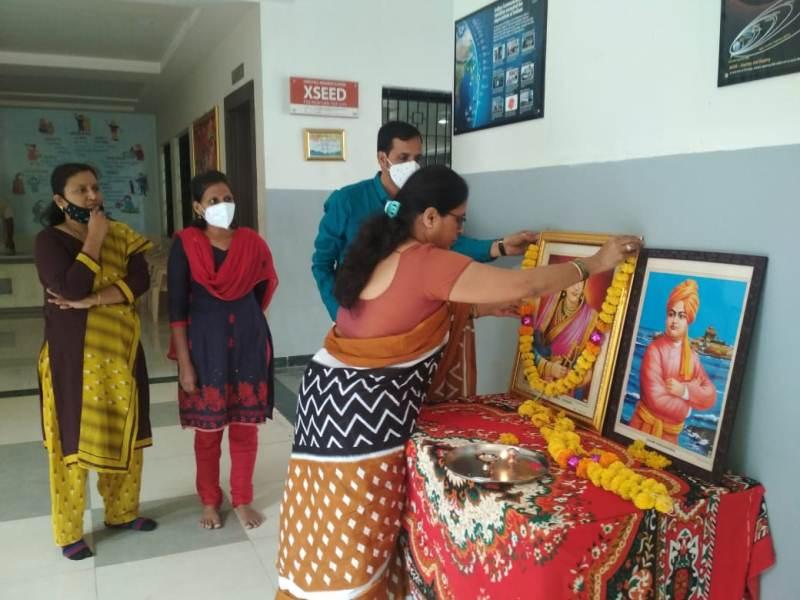 School Principal garlanding the photos of Jijamata