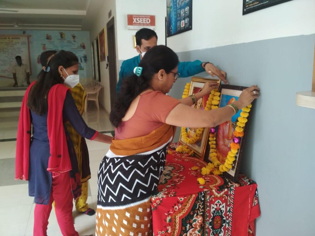 School Principal garlanding the photos of Swami Vivekananda